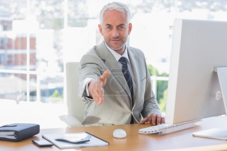 Smiling businessman reaching out hand for handshake