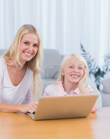Mother and daughter using laptop in the living room