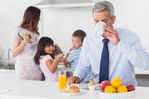 Otec pití kávy, zatímco jeho rodina jsou vaření v kuch