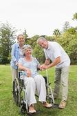 žena sedící na vozíku s manželem a dcerou