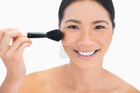 Dark haired young model applying powder on her face