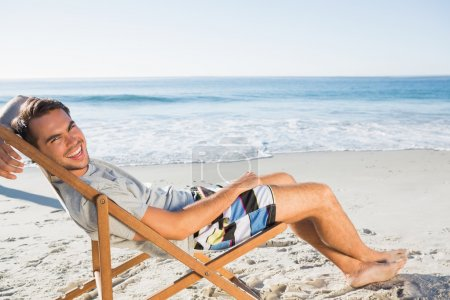Handsome man lying on his deck chair smiling at camera