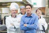 Mladý manažer pózuje s někteří kuchaři