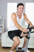 Veselý sportovní muž na kole a poslechu hudby
