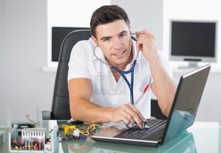 Handsome smiling computer engineer examining laptop with stethoscope