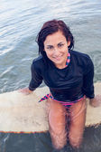 Portrait of a beautiful woman sitting on surfboard in water