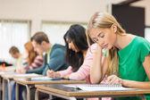 Mladí studenti psaní poznámek v učebně