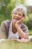 Usměvavá starší žena ležící na park