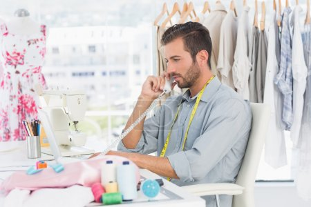 Young male fashion designer using phone