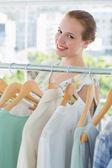 šťastné ženy zákazníka výběrem oblečení v obchodě
