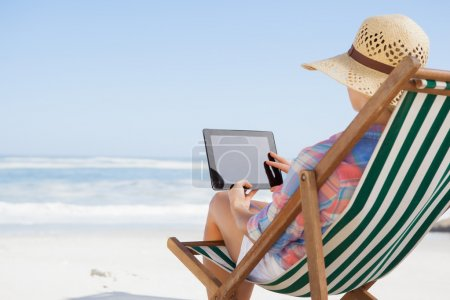 Woman in deck chair using tablet