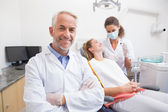 Dentist with assistant and patient