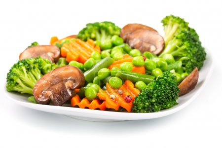 Photo for Mixed vegetables on a plate isolated on white background - Royalty Free Image