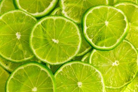 Photo pour Fond vert avec agrumes de tranches de citron vert - image libre de droit