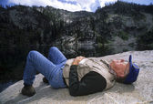 Active senior man napping on a rock