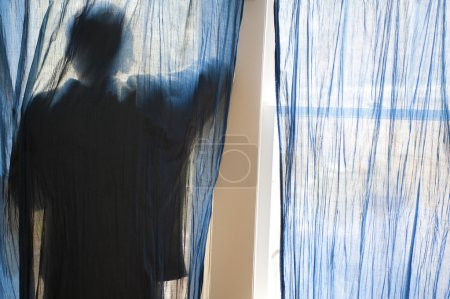 Photo for Young man looking out a window behind blue curtains. - Royalty Free Image