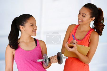 Photo for Woman working out while at the gym with a personal trainer - Royalty Free Image