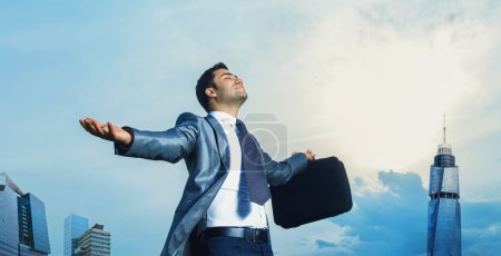 Photo for Successful businessman with arms outstretched celebrating success. Man with arms wide open. Outdoors creative photo - Royalty Free Image