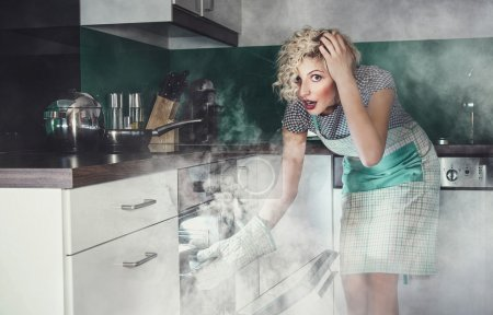 Photo for Creative photo of a astonished woman cook frying lunch in a oven. Smoke, vapor around in the kitchen or home - Royalty Free Image