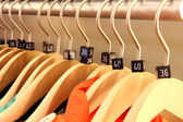 Wooden hangers showing different clothing size tags