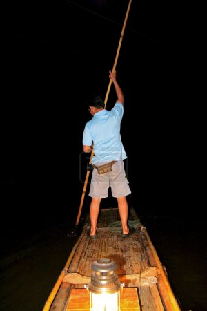 A man standing on a bamboo raft in Maehongson Province, Thailand
