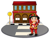 A fireman holding a fire extinguisher in front of the fire stati