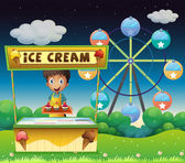 A boy with an icecream stall near the ferris wheel
