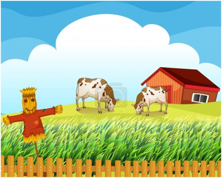 A scarecrow with two cows inside the fence