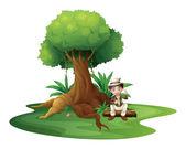 A boy sitting under the big tree