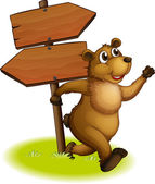 A bear running with a wooden arrow board at the back