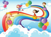 A group of kids playing at the sky with a rainbow