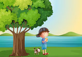 A young boy and his pet under the tree