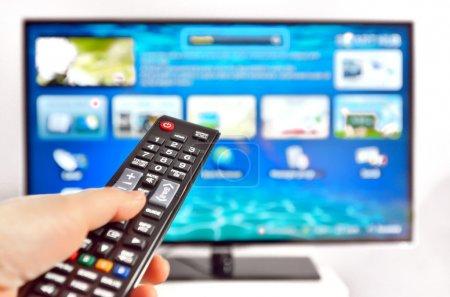 Photo pour Smart tv et télécommande de pressage à la main - image libre de droit