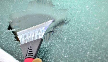 Photo pour Gratter la neige et la glace du pare-brise de la voiture - image libre de droit