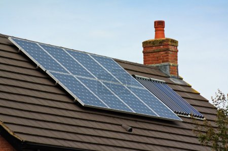 Foto de Paneles solares y de calefacción central fotovoltaicos en el techo de baldosas de la casa residencial - Imagen libre de derechos