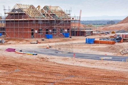Photo pour Site de construction de logements résidentiels partiellement construits avec des maisons aux premiers stades de construction - image libre de droit