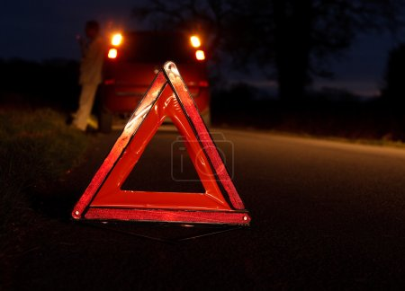 Photo for Car driver awaits recovery after experiencing a vehicle breakdown at night with warning triangle - Royalty Free Image