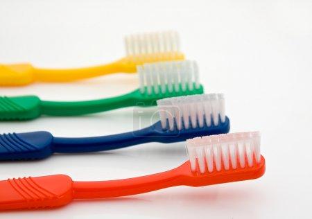 Photo pour Détail d'une rangée de brosses à dents de différentes couleurs avec l'avant une mise au point sélective bon pour les dentistes - image libre de droit