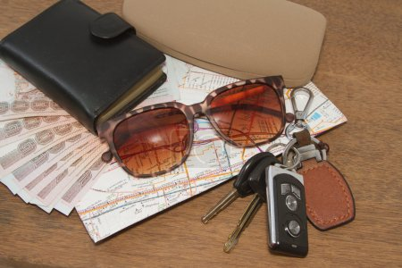 Keys and sunglasses on a road map with pocket money,Ready to tra