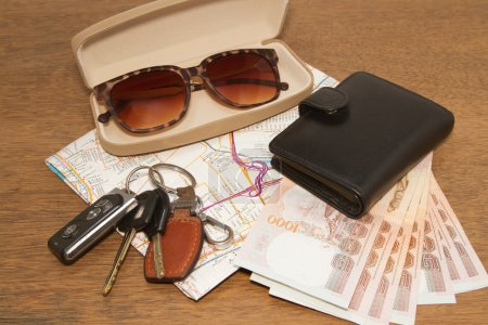 Keys and sunglasses on a road map with pocket money,Ready to tr