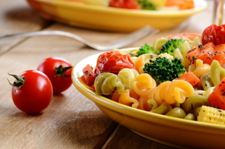 Photo for Pasta fusilli salad with broccoli, carrot, corn, and tomatoes on the kitchen table - Royalty Free Image