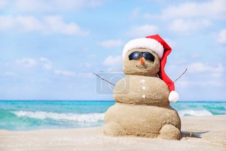 Photo for Smiling sandy snowman in red santa hat on the sea beach. Holiday concept can be used for New Year and Christmas Cards - Royalty Free Image
