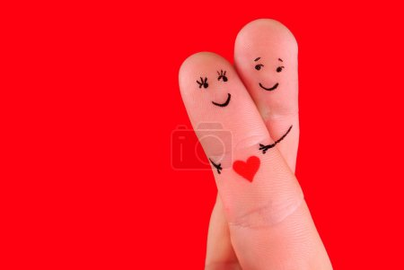 Photo for Happy couple concept - a man and a woman hug,painted at fingers isolated on red background - Royalty Free Image