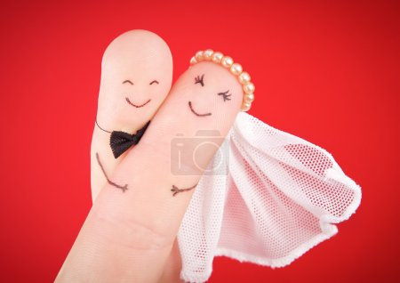 Wedding concept - newlyweds painted at fingers against red back