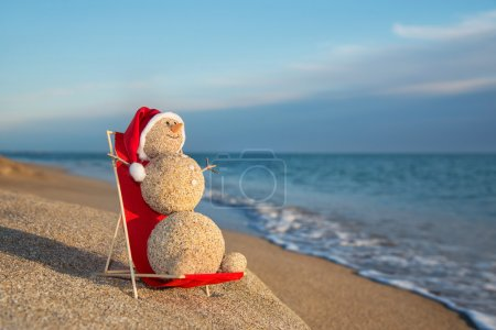 Photo for Sandy snowman in santa hat sunbathing in beach lounge. Holiday concept for New Years and Christmas Cards. - Royalty Free Image