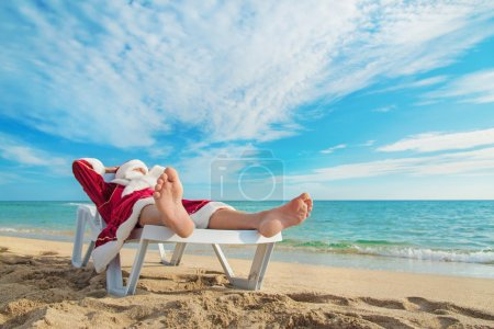 Photo for Sunbathing Santa Claus relaxing in bedstone on tropical sandy beach - Christmas concept - Royalty Free Image