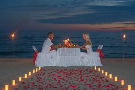 Foto de Young couple share a romantic dinner with candles, torches and way or rose petals on sea sandy beach against sunset - wedding day, proposal of marriage or honeymoon concept - Imagen libre de derechos