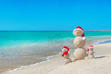 Snowmans family at sea beach in santa hat.
