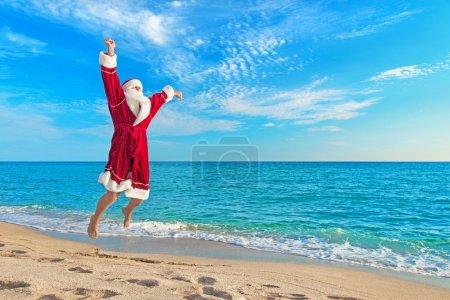 Santa Claus flying against sea beach - Christmas concept