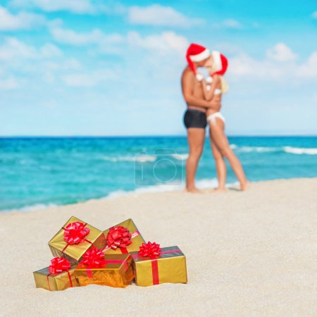 Kissing couple in santa hats at sea beach with christmas golden